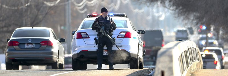 A West Valley City Police officer watches I-215 at 700 east following a shooting at Fashion Place Mall in Murray, Utah on Sunday, Jan. (Steve Griffin/The Deseret News via AP)