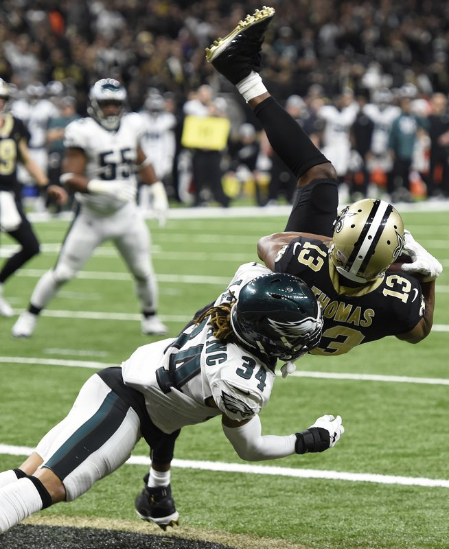 New Orleans Saints wide receiver Michael Thomas (13) pulls in a touchdown reception against Philadelphia Eagles cornerback Cre'von LeBlanc (34) in the second half of an NFL divisional playoff football game in New Orleans, Sunday, Jan. (AP Photo/Bill Feig)