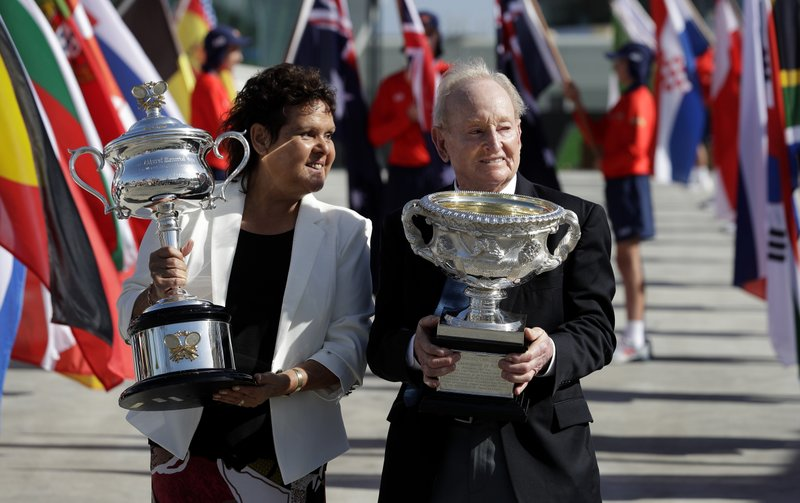 Australian tennis legends Evonne Goolagong Cawley and Rod Laver hold the women's and men's trophies, the Daphne Akhurst Memorial Cup and the Norman Brookes Challenge Cup at the official start of the Australian Open tennis championships in Melbourne, Australia, Monday, Jan. (AP Photo/Aaron Favila)