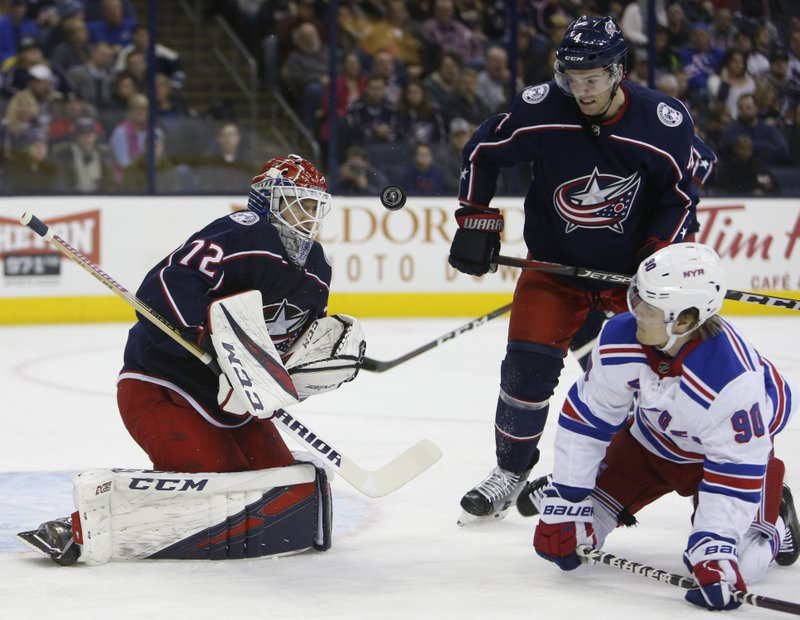 Columbus Blue Jackets' Sergei Bobrovsky, left, of Russia, makes a save in front of teammate Scott Harrington, center, and New York Rangers' Vladislav Namestnikov, also of Russia, during the first period of an NHL hockey game Sunday, Jan. (AP Photo/Jay LaPrete)