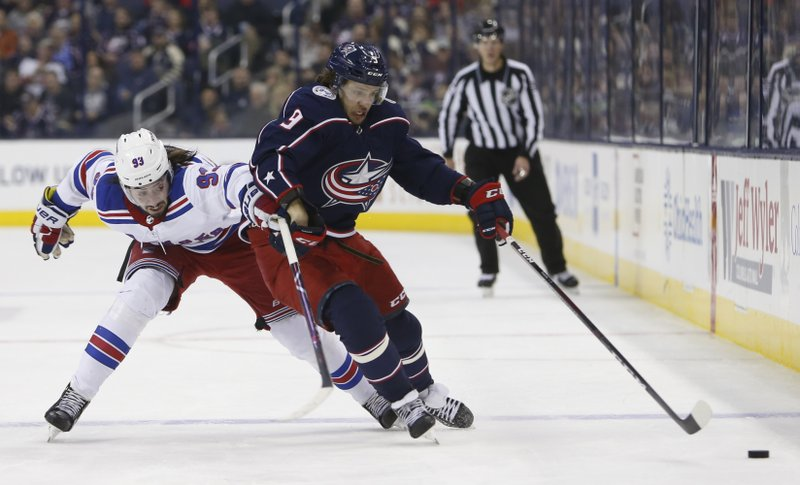 Columbus Blue Jackets' Artemi Panarin, right, of Russia, carries the puck across the blue line as New York Rangers' Mika Zibanejad, of Sweden, pursues during the second period of an NHL hockey game Sunday, Jan. (AP Photo/Jay LaPrete)