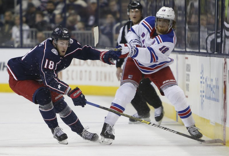 New York Rangers' Marc Staal, right, passes the puck in front of Columbus Blue Jackets' Pierre-Luc Dubois during the first period of an NHL hockey game Sunday, Jan. (AP Photo/Jay LaPrete)