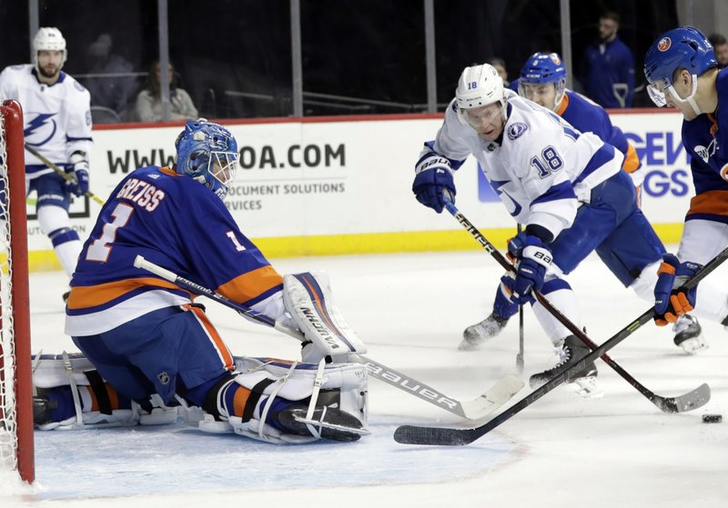 Tampa Bay Lightning's Ondrej Palat (18) attempts to score as New York Islanders goaltender Thomas Greiss (1) defends during the first period of an NHL hockey game Sunday, Jan. (AP Photo/Frank Franklin II)