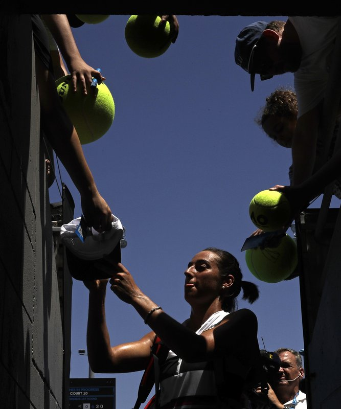 France's Caroline Garcia signs autographs after defeating compatriot Jessika Ponchet during their first round match at the Australian Open tennis championships in Melbourne, Australia, Monday, Jan. (AP Photo/Kin Cheung)