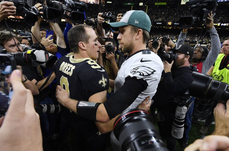 New Orleans Saints quarterback Drew Brees (9) speaks with Philadelphia Eagles quarterback Nick Foles after an NFL divisional playoff football game in New Orleans, Sunday, Jan. (AP Photo/Bill Feig)