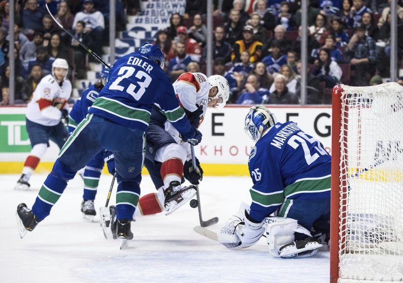 Vancouver Canucks' Alexander Edler (23), of Sweden, checks Florida Panthers' Aleksander Barkov, center, of Finland, as he attempts a shot against Vancouver Canucks goalie Jacob Markstrom (25), of Sweden, during the first period of an NHL hockey game in Vancouver, British Columbia, Sunday, Jan. (Darryl Dyck/The Canadian Press via AP)