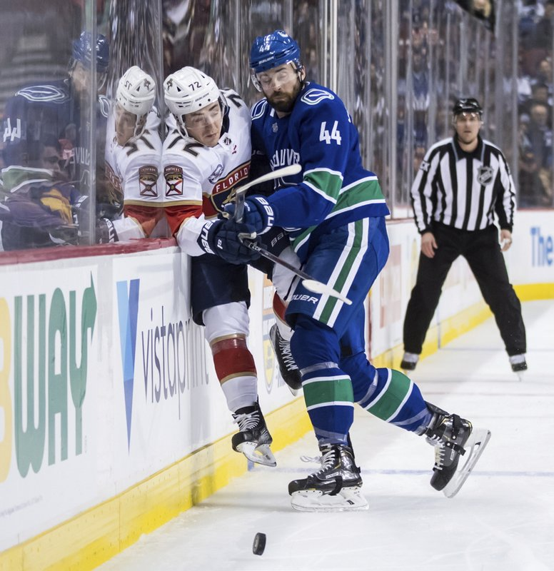 Vancouver Canucks' Erik Gudbranson (44) checks Florida Panthers' Frank Vatrano (72) during the first period of an NHL hockey game in Vancouver, British Columbia, Sunday, Jan. (Darryl Dyck/The Canadian Press via AP)