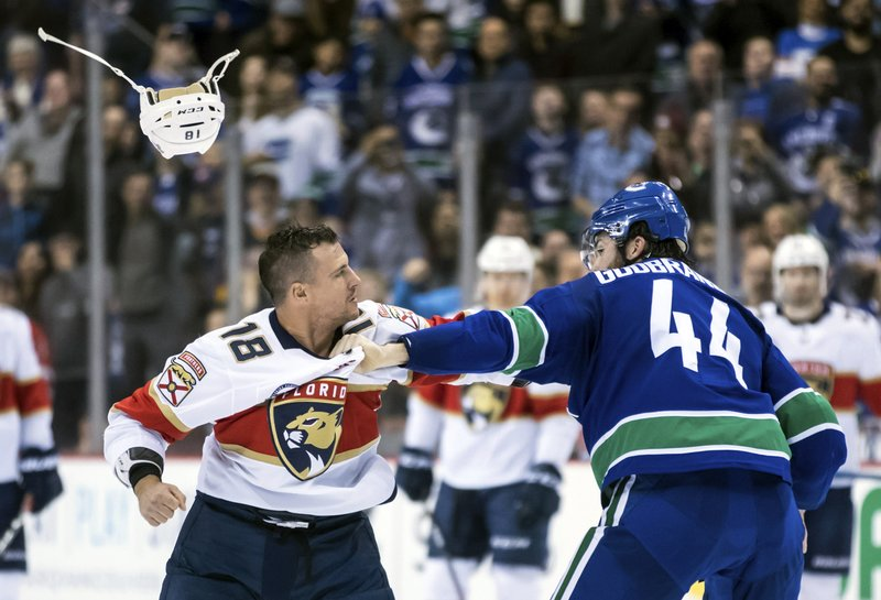 Florida Panthers' Micheal Haley (18) loses his helmet as he fights with Vancouver Canucks' Erik Gudbranson (44) during the first period of an NHL hockey game in Vancouver, British Columbia, Sunday, Jan. (Darryl Dyck/The Canadian Press via AP)