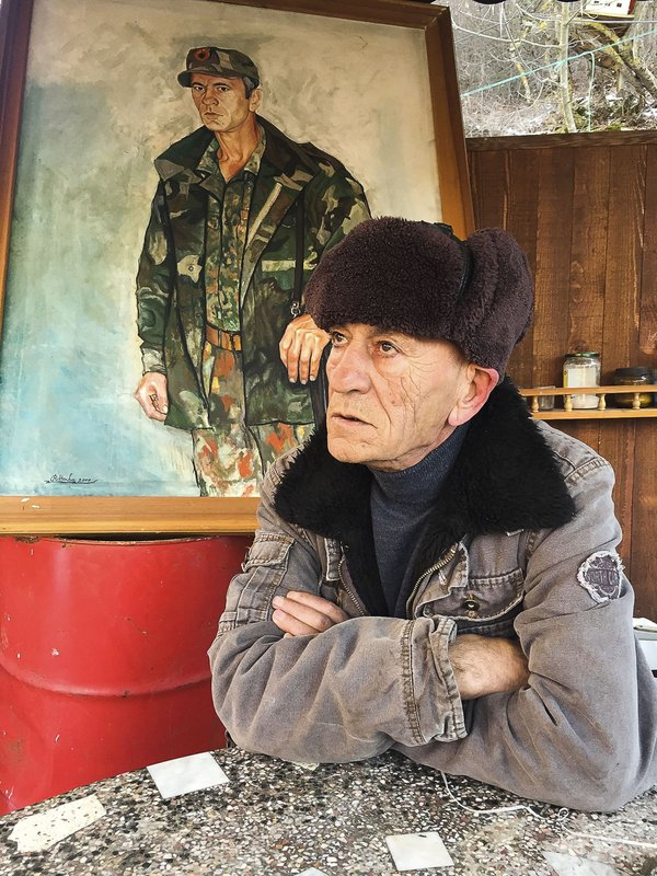 In this Monday, Jan. 7, 2019 photo, former Kosovo Liberation Army fighter Sabahajdin Cena poses for a photo in front of a painted portrait of himself, in the town of Rahovec. (50 miles) west of the capital, Pristina, during the war. (AP Photo/Visar Kryeziu)