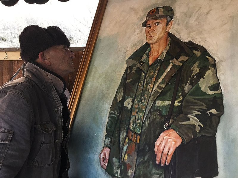 In this Monday, Jan. 7, 2019 photo, former Kosovo Liberation Army fighter Sabahajdin Cena looks a painted portrait of himself, in the town of Rahovec. (50 miles) west of the capital, Pristina, during the war. (AP Photo/Visar Kryeziu)