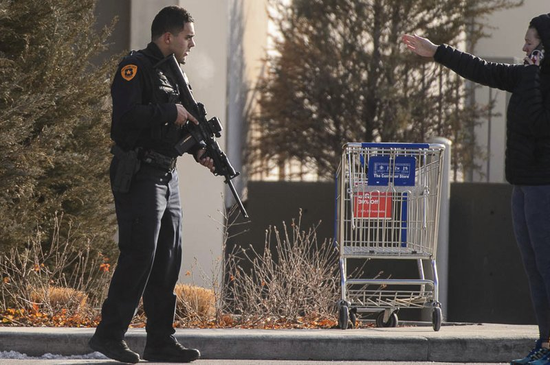 A law enforcement officer directs people outside the Fashion Place mall after a shooting in Murray, Utah, Sunday, Jan. (Trent Nelson/The Salt Lake Tribune via AP)