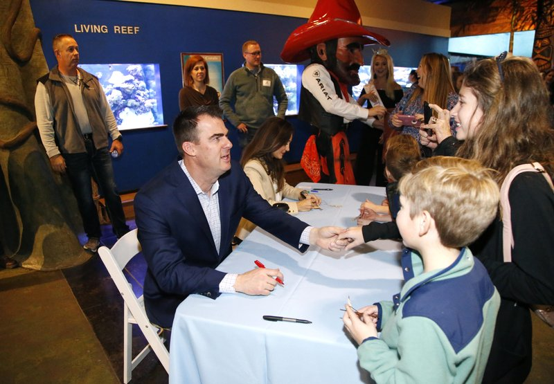 Governor-elect Kevin Stitt (left) greets Harrison Pawelka and his sister Mary Caroline Pawelka (right) during a pre-inaugural event at the Oklahoma Aquarium in Jenks, Okla. (Matt BarTulsa World/Tulsa World via AP)