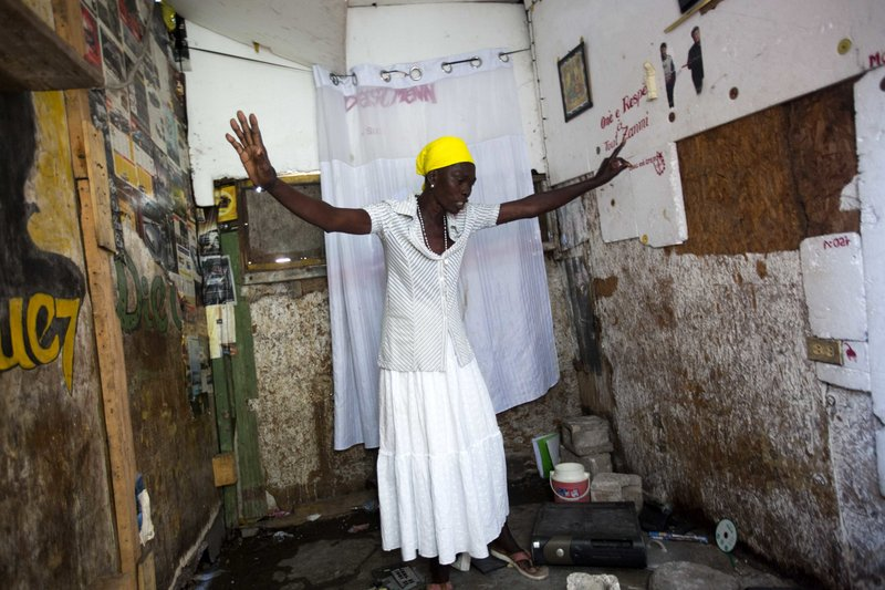 In this Dec. 6, 2018 photo, Marie-Lourdes Corestan asks herself out loud how will she survive without her son, in his room after he was slain during the La Saline massacre in Port-au-Prince, Haiti. (AP Photo/Dieu Nalio Chery)