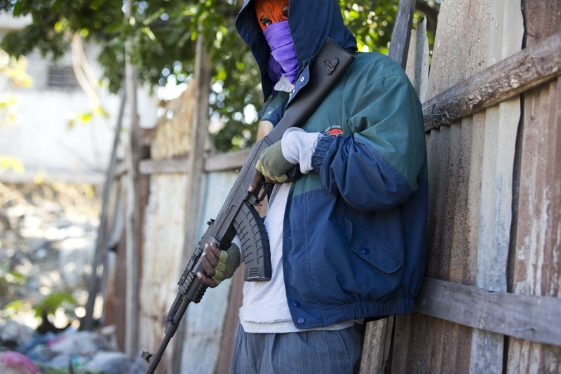 In this Dec. 16, 2018 photo, an armed gang member poses for a picture on the south side of La Saline slum in Port-au-Prince, Haiti, almost a month after a massacre on Nov. (AP Photo/Dieu Nalio Chery)