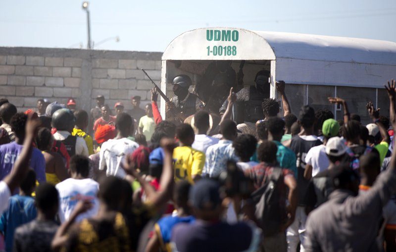 In this Dec. 10, 2018 photo, police guard an alleged gang member to keep the crowd from attacking him outside a police station in the La Saline slum of Port-au-Prince, Haiti. (AP Photo/Dieu Nalio Chery)
