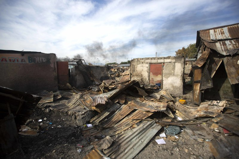 In this Nov. 21, 2018 photo, homes that were burned to the ground during a massacre lay in ruins in the La Saline slum of Port-au-Prince, Haiti. (AP Photo/Dieu Nalio Chery)