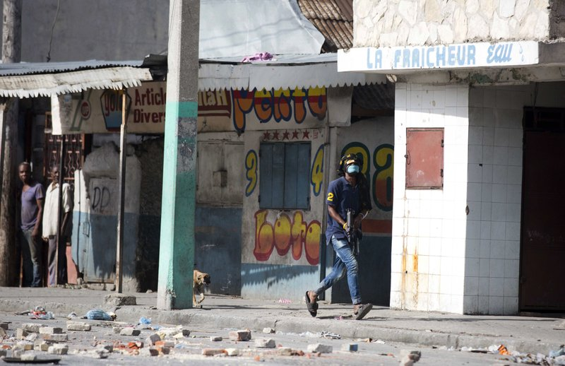 In this Nov. 21, 2018 photo, an armed civilian runs during a shootout between rival gangs trying to take control of the Croix-des-Bossales market on Boulevard Jean-Jacques Dessalines, a main commercial artery of Port-au-Prince, Haiti. (AP Photo/Dieu Nalio Chery)
