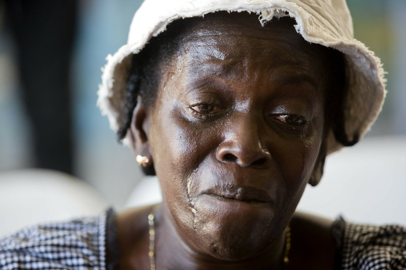 In this Dec. 13, 2018 photo, Jeannette Jasmin, mother of 21-year-old Claudy Thomas, who Jasmine said was killed during a massacre that killed at least 20 people in the La Saline slum, cries during a memorial for the victims in Port-au-Prince, Haiti. (AP Photo/Dieu Nalio Chery)