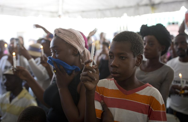In this Dec. 13, 2018 photo, Wilky Coby, 16, who was shot four times but survived the La Saline massacre, holds up a candle during a memorial for the victims in Port-au-Prince, Haiti. (AP Photo/Dieu Nalio Chery)
