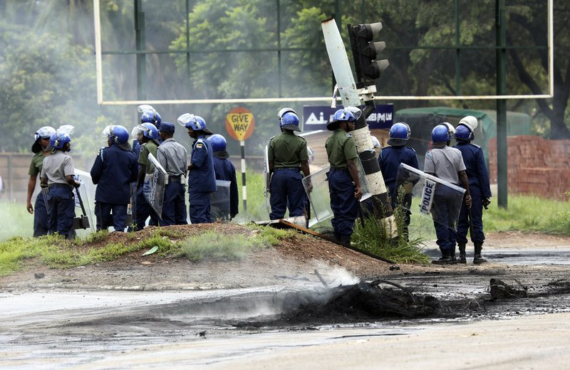 Riot police on the streets during protests over the hike in fuel prices in Harare, Zimbabwe, Monday, Jan. (AP Photo/Tsvangirayi Mukwazhi)