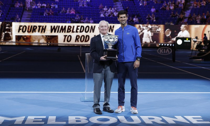 Serbia's Novak Djokovic, right, presents a trophy to Rod Laver during the 50th anniversary celebration for Australian Open and Rod Laver's second Grand Slam at the Australian Open tennis championships in Melbourne, Australia, Monday, Jan. (AP Photo/Aaron Favila)