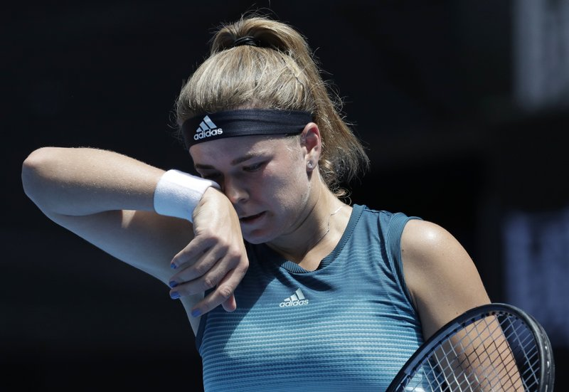Karolina Muchova of the Czech Republic wipes the sweat from her face during her first round match against compatriot Karolina Pliskova at the Australian Open tennis championships in Melbourne, Australia, Tuesday, Jan. (AP Photo/Aaron Favila)