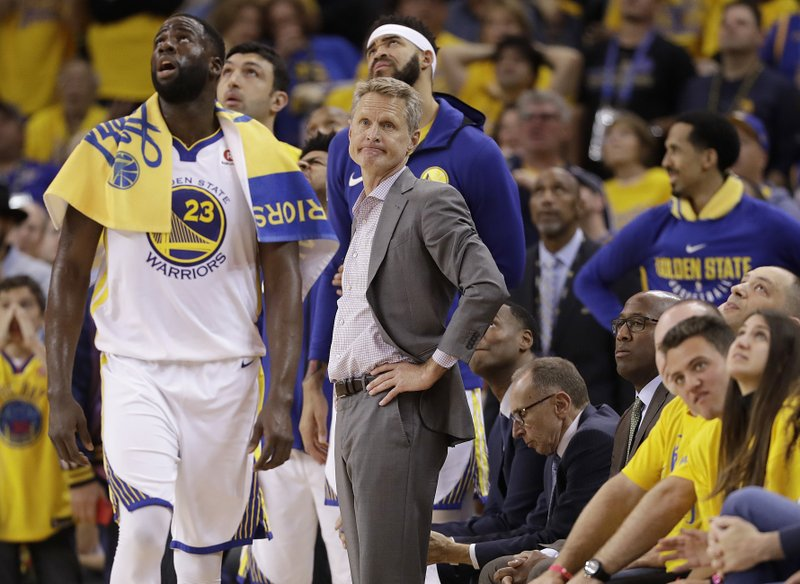 FILE - In this May 20, 2018 file photo, Golden State Warriors head coach Steve Kerr, center, watches during the first half of Game 3 of the NBA basketball Western Conference Finals against the Houston Rockets in Oakland, Calif. (AP Photo/Marcio Jose Sanchez, File)