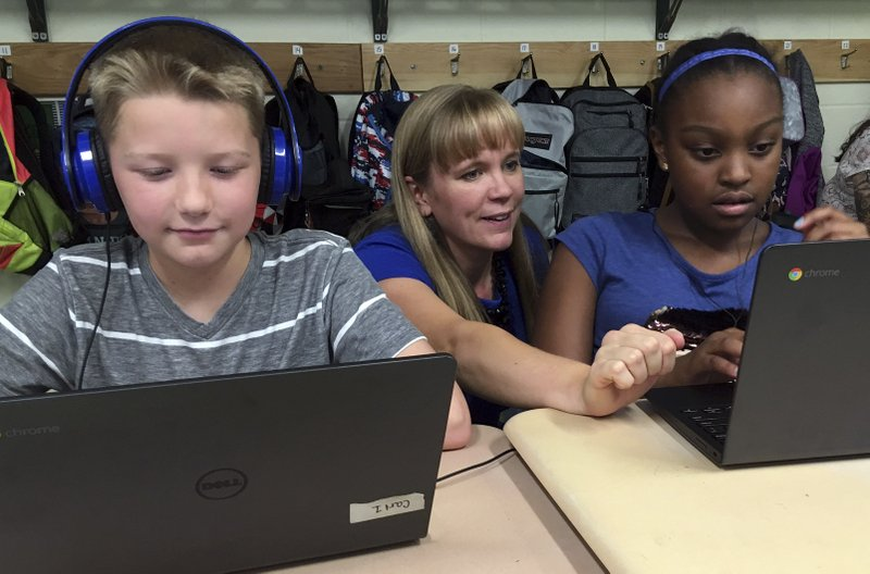 In this Sept. 20, 2018 photo, fifth grade teacher Heather Dalton, center, works with students Julian Ryno, left, and Ma'Kenley Burns, doing math problems on the DreamBox system at Charles Barnum Elementary School in Groton, Conn. (AP Photo/Michael Melia)