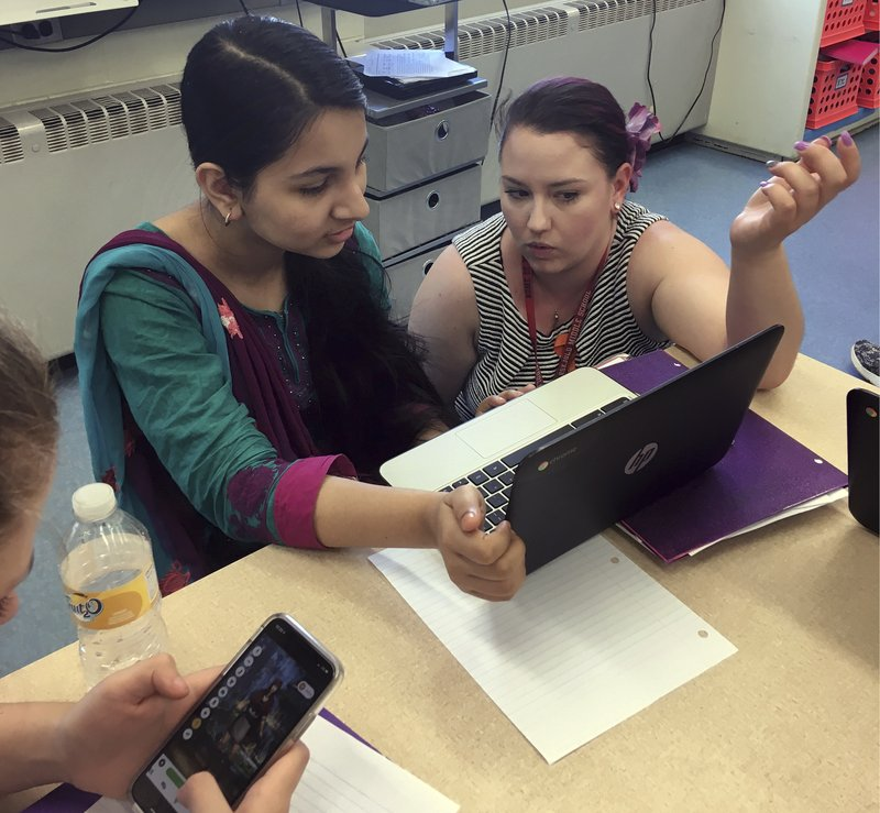 In this May 23, 2018 photo, teacher Gianna Gurga, right, talks with student Maisha Chowdhury Jabia in a class on financial literacy at Dag Hammarskjold Middle School in Wallingford, Conn. (AP Photo/Michael Melia)