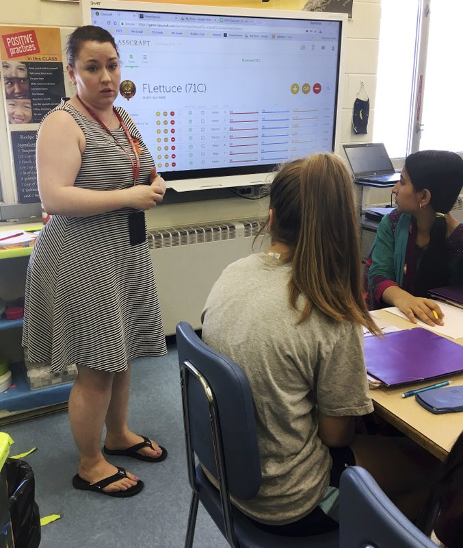 In this May 23, 2018 photo, teacher Gianna Gurga, left, speaks to students Faith Broadway, center, and Maisha Chowdhury Jabia, right, as she leads a class on financial literacy at Dag Hammarskjold Middle School in Wallingford, Conn. (AP Photo/Michael Melia)