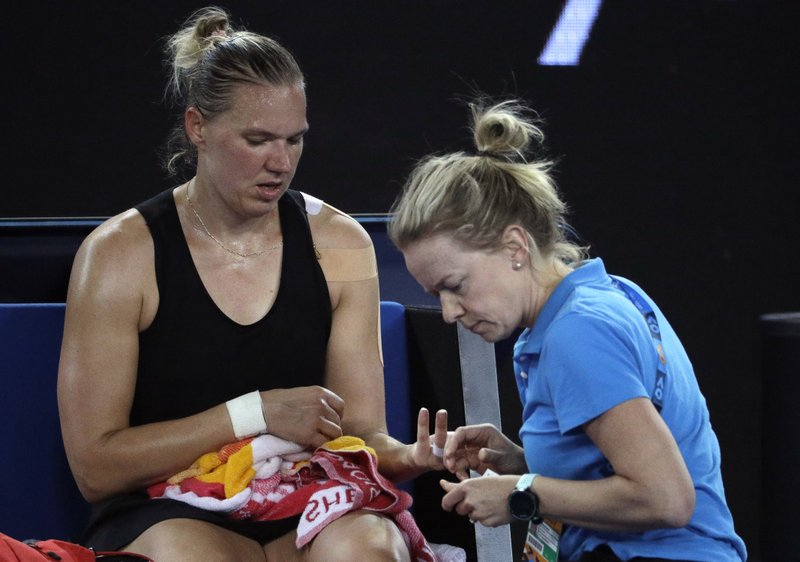 Estonia's Kaia Kanepi receives treatment from a trainer during her first round match against Romania's Simona Halep at the Australian Open tennis championships in Melbourne, Australia, Tuesday, Jan. (AP Photo/Mark Schiefelbein)