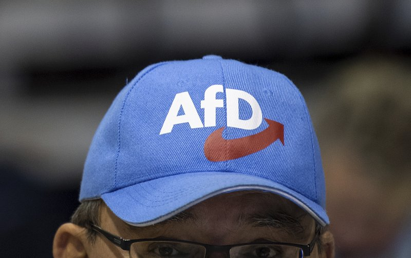 FILE - In this Sunday, Jan. 13, 2019 file photo a participant of the European election meeting of the Alternative for Germany party, AfD, wears a cap with the party's logo in the Saxony-Arena in Riesa, Germany. (Monika Skolimowska/dpa via AP, file)