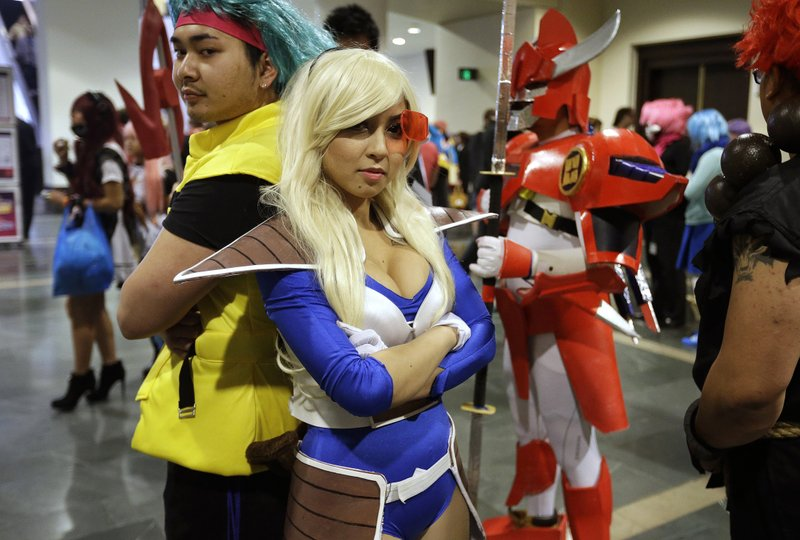 FILE - In this April 5, 2015 file photo, participants at Anime Boston, Threa Srey, of Lowell, Mass., left, dressed as Bulma from the Japanese animated series