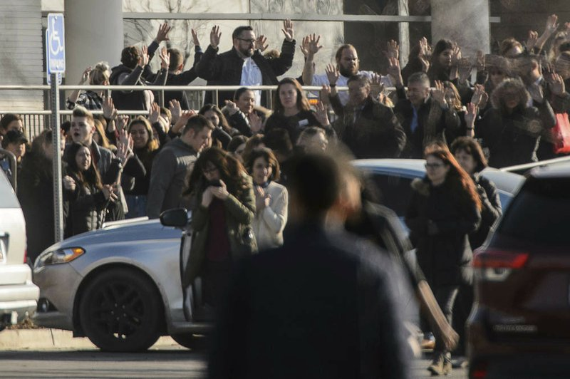 (Trent Nelson | The Salt Lake Tribune) People evacuate with their hands aloft after a shooting at the Fashion Place Mall in Murray on Sunday Jan. (Trent Nelson/The Salt Lake Tribune via AP)
