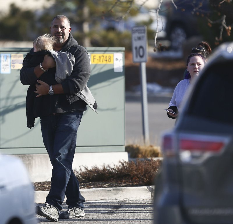 A man holding a child leaves the Fashion Place mall as police investigate a shooting at Fashion Place in Murray, Utah on Sunday, Jan. (Silas Walker/The Deseret News via AP)