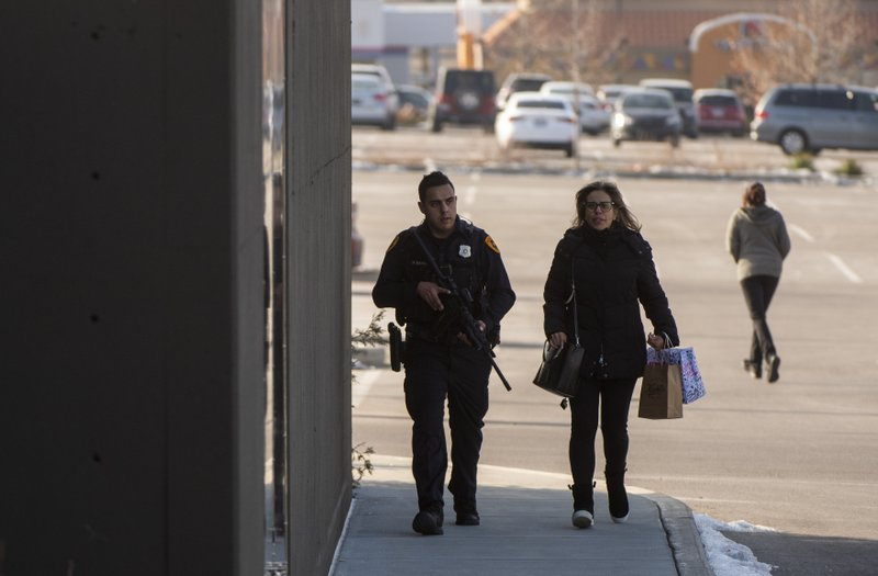 (Rick Egan | The Salt Lake Tribune) A police officer escorts a shopper to her car after a shooting at the Fashion Place Mall in Murray, Utah, on Sunday, Jan. (Rick Egan/The Salt Lake Tribune via AP)