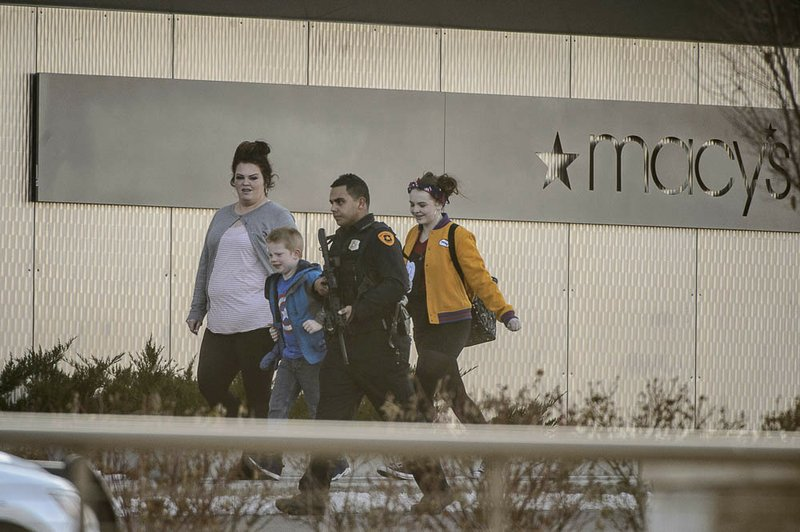 (Trent Nelson | The Salt Lake Tribune) Armed law enforcement escort people after a shooting at the Fashion Place Mall in Murray on Sunday Jan. (Trent Nelson/The Salt Lake Tribune via AP)