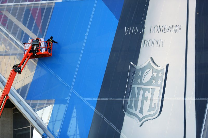 FILE - In this Thursday, Jan. 10, 2019, file photo, workers hang banners on Mercedes-Benz Stadium in preparation for the NFL Super Bowl football game, in Atlanta. (AP Photo/John Bazemore, File)