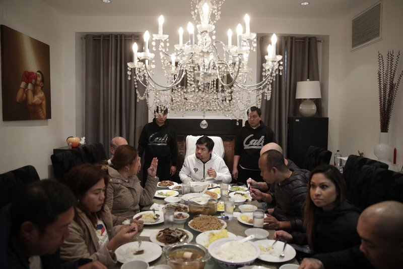 Boxer Manny Pacquiao, center, eats his breakfast with friends and relatives following his morning run Monday, Jan. (AP Photo/Jae C. Hong)