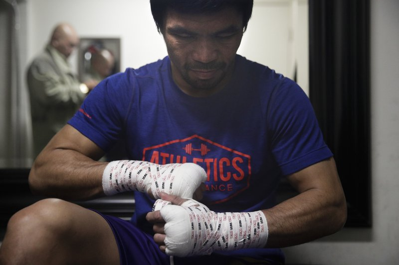 Boxer Manny Pacquiao tapes his hands for a workout at the Wild Card Boxing Club Monday, Jan. 14, 2019, in Los Angeles. (AP Photo/Jae C. Hong)