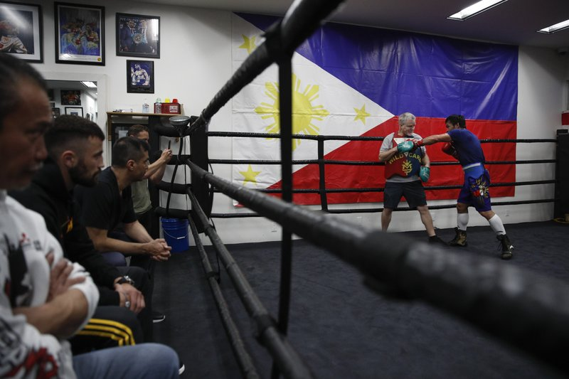 Boxer Manny Pacquiao, far right, trains with Freddie Roach at the Wild Card Boxing Club Monday, Jan. 14, 2019, in Los Angeles. (AP Photo/Jae C. Hong)