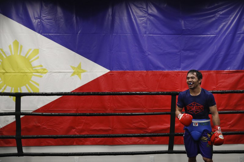 Standing in front of a large Filipino flag, boxer Manny Pacquiao smiles while training at the Wild Card Boxing Club Monday, Jan. (AP Photo/Jae C. Hong)
