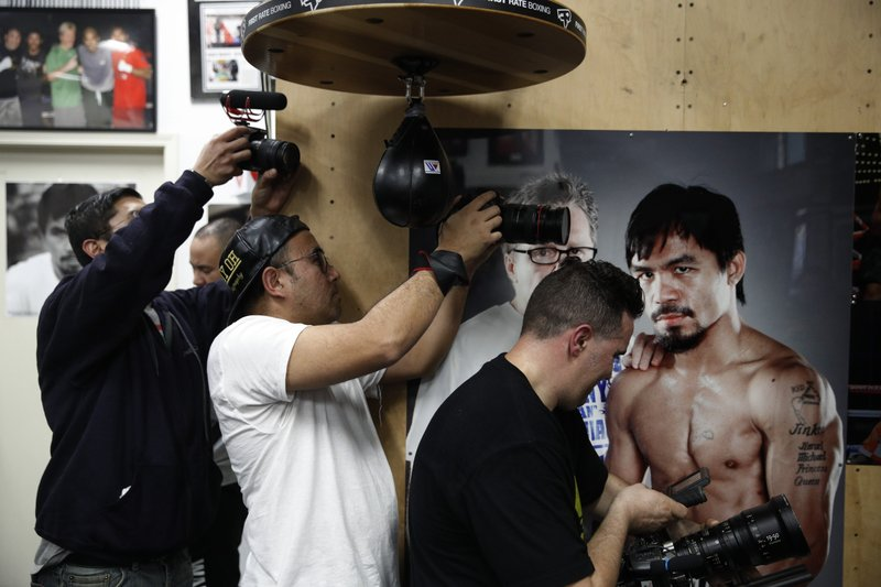 Film production crew members record as boxer Manny Pacquiao, not pictured, hits a speed bag at the Wild Card Boxing Club Monday, Jan. (AP Photo/Jae C. Hong)