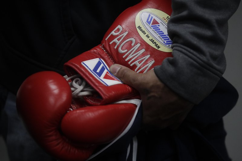 A trainer holds boxer Manny Pacquiao's gloves with Pacquiao's nickname embroidered on them at the Wild Card Boxing Club Monday, Jan. (AP Photo/Jae C. Hong)