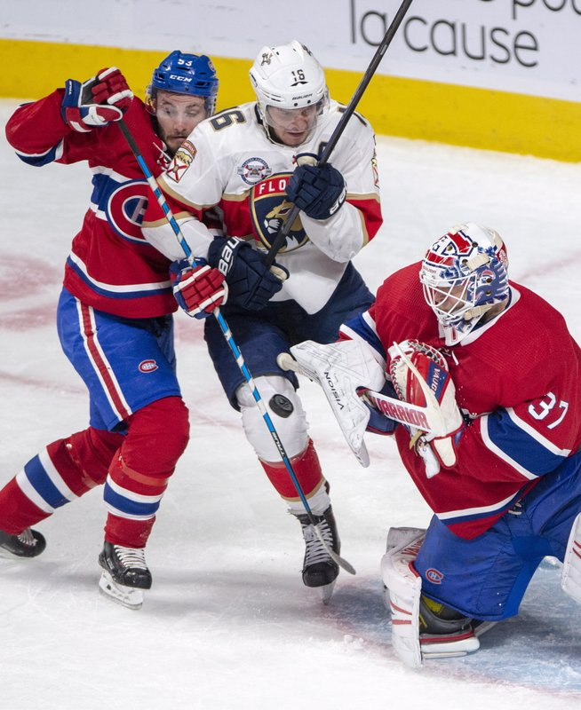 Florida Panthers center Aleksander Barkov (16) is sandwiched between Montreal Canadiens defenseman Victor Mete (53) and Montreal Canadiens goaltender Antti Niemi (37) during the first period of an NHL hockey game, Tuesday, Jan. (Ryan Remiorz/The Canadian Press via AP)