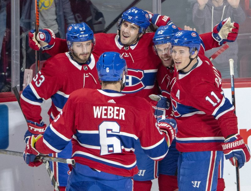 Montreal Canadiens center Phillip Danault (24) celebrates with teammates Shea Weber (6), Victor Mete (53), Jonathan Drouin (92) and Brendan Gallagher (11) after scoring against the Florida Panthers during the second period of an NHL hockey game, Tuesday, Jan. (Ryan Remiorz/The Canadian Press via AP)