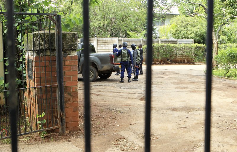 Armed police officers stand outside the residence of Evan Mawarire, an activist and pastor who helped mobilize people to protest against the hike in fuel prices, following his arrest in Harare, Zimbabwe, Wednesday, Jan. (AP Photo/Tsvangirayi Mukwazhi)