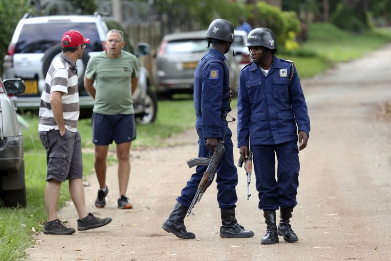 Neighbours watch as armed police surround the residence of Evan Mawarire, an activist and pastor who helped mobilize people to protest against the hike in fuel prices, following his arrest in Harare, Zimbabwe, Wednesday, Jan. (AP Photo/Tsvangirayi Mukwazhi)