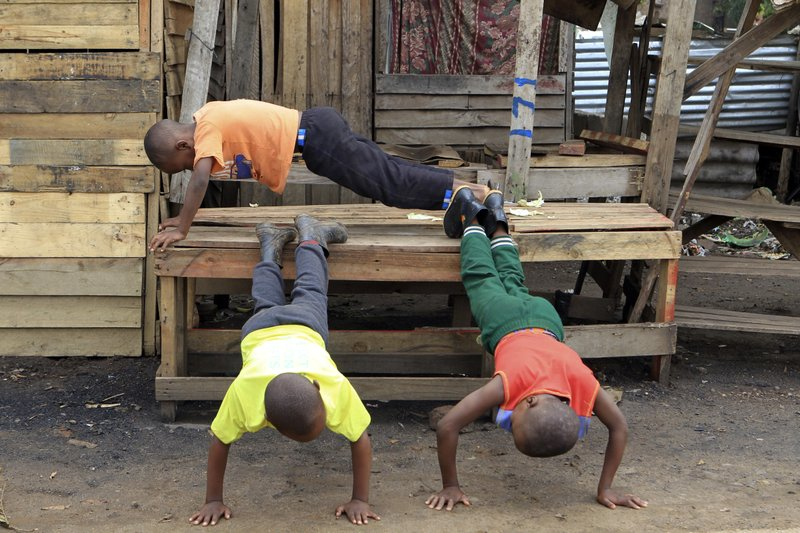 Children use a deserted market stall into an exercise bench as business came to a standstill on the third day of protests over the hike in fuel prices in Harare, Zimbabwe, Wednesday, Jan. (AP Photo/Tsvangirayi Mukwazhi)