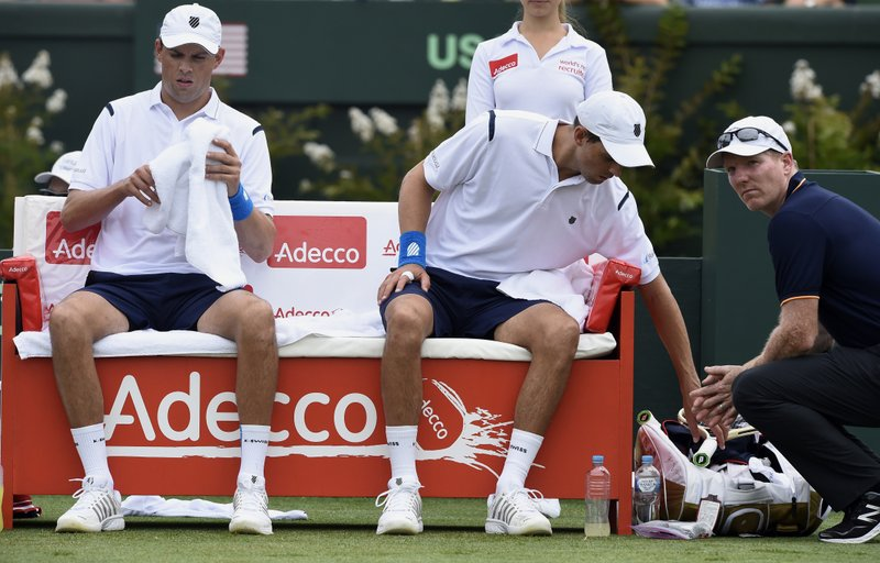 FILE - In this March 5, 2016 file photo, Jim Courier, far right, captain of the United States Davis Cup team, talks to doubles players Bob, left, and Mike Bryan while playing against Australia's Lleyton Hewitt and John Peers during their Davis Cup doubles match in Melbourne, Australia. (4), 7-6 (1) win over Alex Bolt and Marc Polmans at the Australian Open in Melbourne, Australia, Wednesday Jan. 16, 2019. (AP Photo/Andrew Brownbill,File)